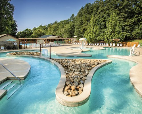 A scenic view of an outdoor lazy river surrounded by a wooded area.