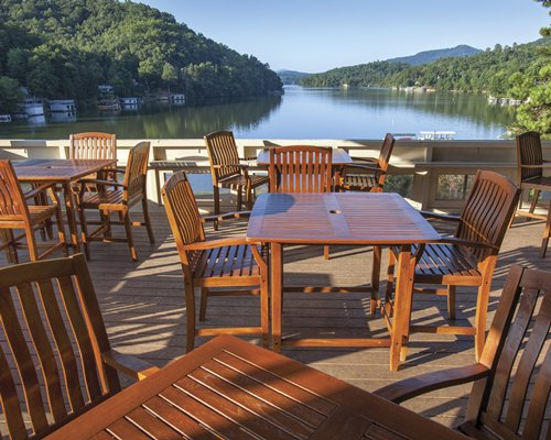 A large outdoor dining area with multiple tables and a view of the water.