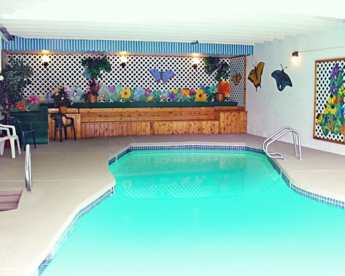 Indoor swimming pool with patio chairs.