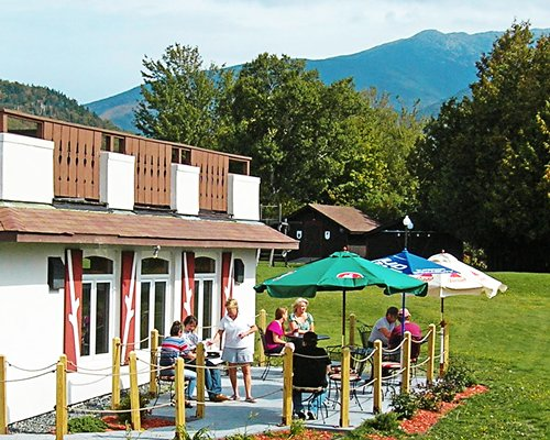 Outdoor restaurant with sunshades and patio chairs and mountains.