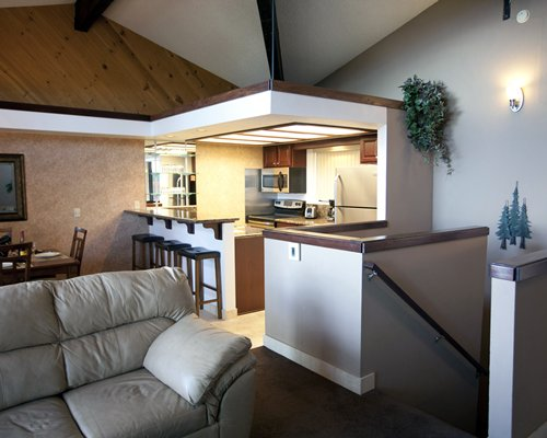 An open plan dining living and kitchen area with a breakfast bar.