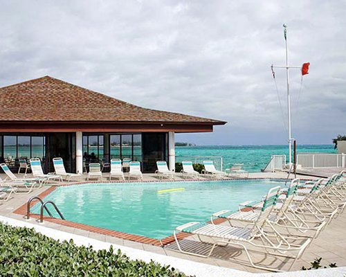 An outdoor swimming pool with chaise lounge chairs alongside resort villas and the ocean.