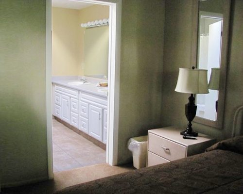 A furnished bedroom with a double sink vanity.