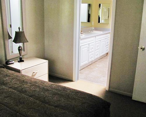 A bedroom with queen sized bed and a bathroom with double sink vanity.