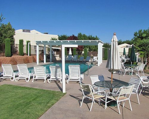 Outdoor pool with chaise lounge chairs and patio tables with umbrellas..