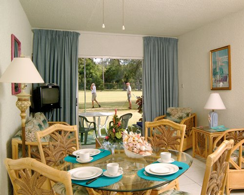 An open plan living room with dining area television and view of golfers at the golf course.
