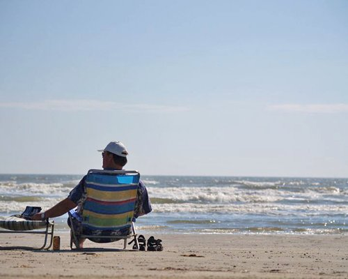 A man sitting on the chair facing the beach.