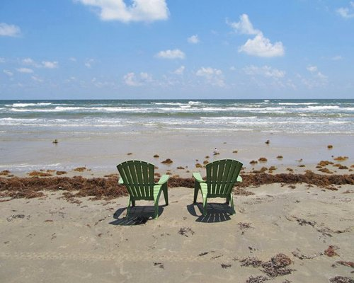 A pair of chairs on the beach facing the ocean.