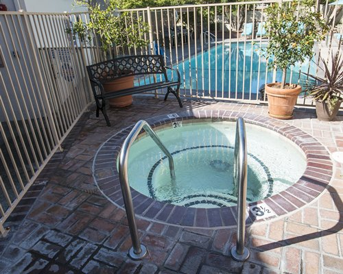 Outdoor hot tub alongside swimming pool.