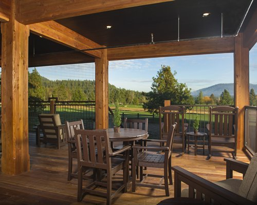 Dining area with a view of golf course trees and mountain.