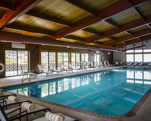 A large indoor swimming pool with lounge access.