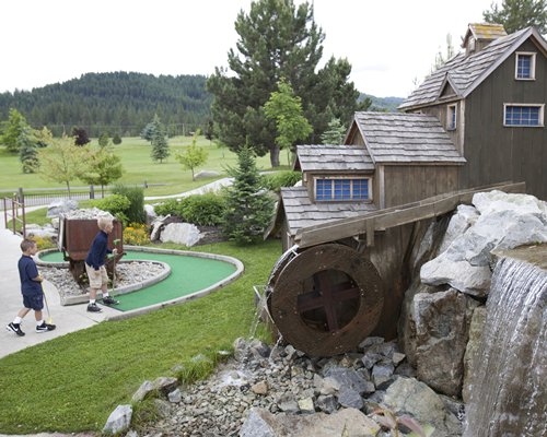 Miniature golf course with fountain and forest view.
