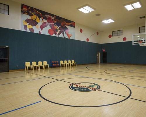 An indoor basket ball court along with chairs.