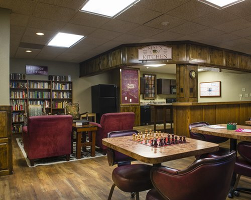 An open plan kitchen alongside a library and chess board tables.