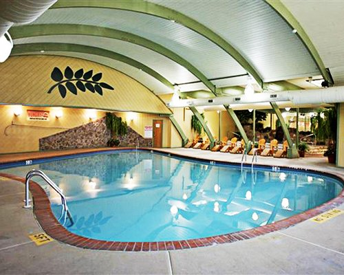 Indoor swimming pool with lounge chairs.