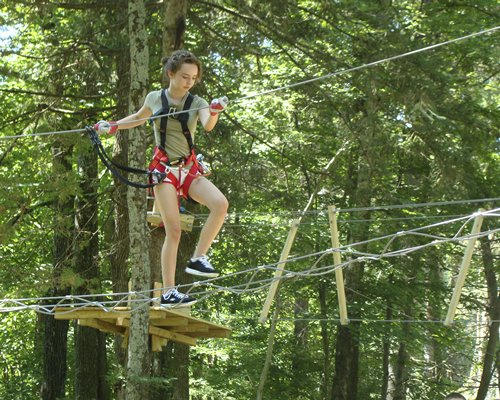 A woman on the ropes course and ziplines surrounded by trees.