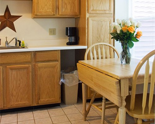 A well equipped kitchen and wooden dining table.