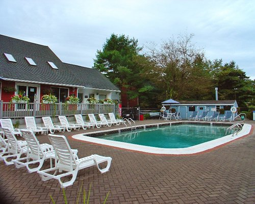 Outdoor swimming pool with chaise lounge chairs and patio table.