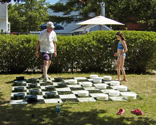 Man and a child playing a huge version of checkers in the lawn.