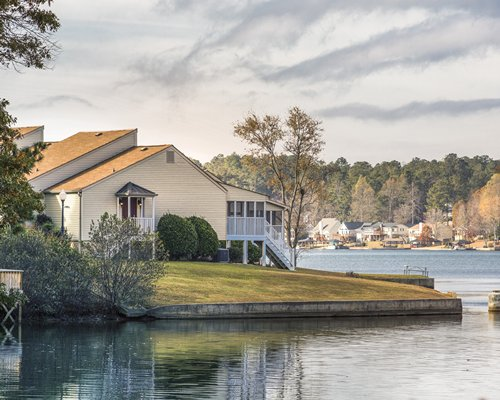 A lake view of Fairfield Plantation resort surrounded by lawns and trees.