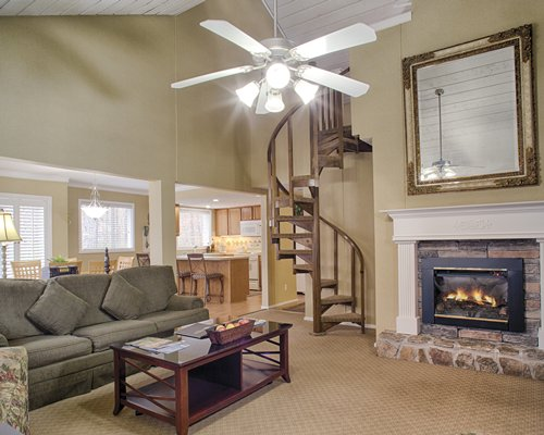 A well furnished living room with a spiral staircase and fireplace.