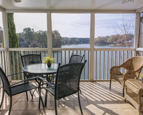 A balcony area with a view of the lake and woods.