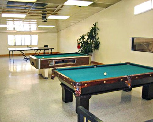 An indoor playing area wit table tennis and pool tables.