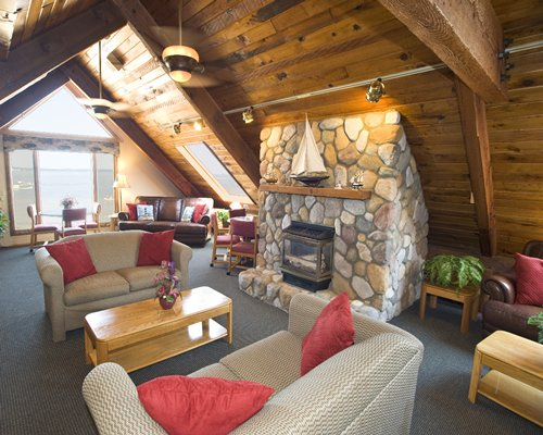A wood paneled living room with double pull out sofa and stone fireplace.