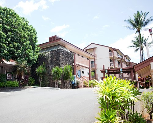 A street view of Banyan Harbor resort surrounded by shrubs and trees.
