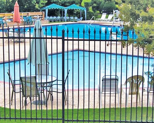 Outdoor swimming pool for adults and kids with chaise lounge chairs and patio tables.
