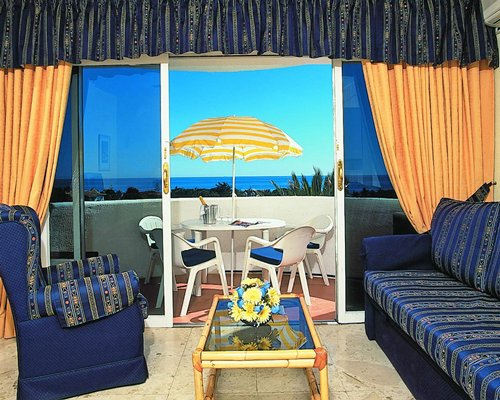 Furnished living room and balcony with patio furniture and ocean view.