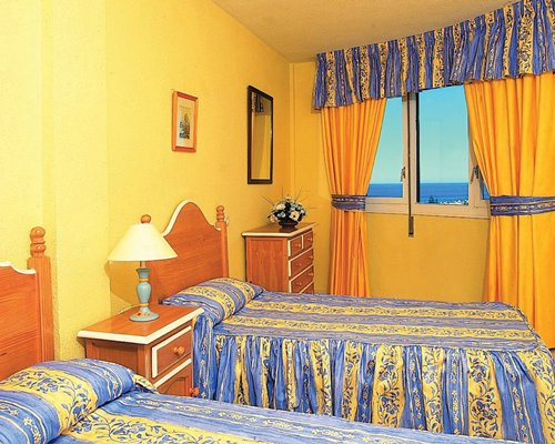 Furnished bedroom with two twin beds and ocean view.