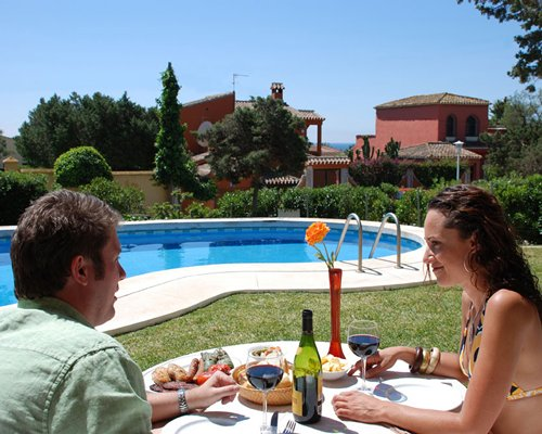 A couple dining near an outdoor swimming pool.
