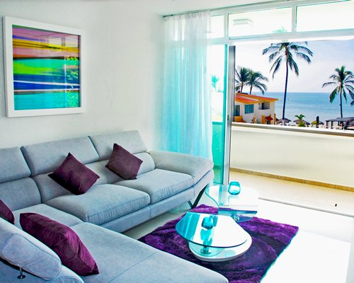 A furnished living room facing the ocean with a balcony.