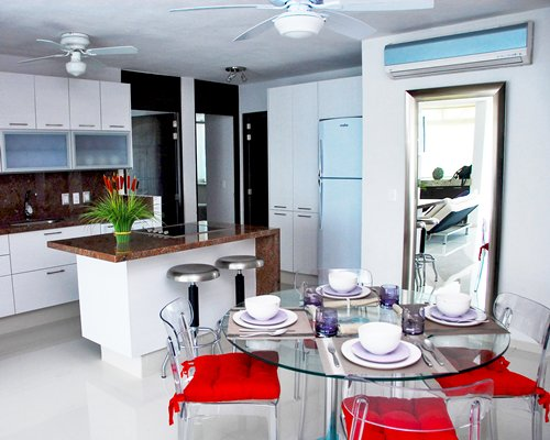 An open plan kitchen with glass top dining table.