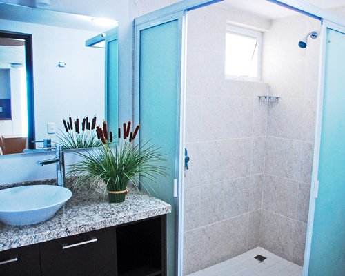 A bathroom with single sink vanity and a stand up shower.