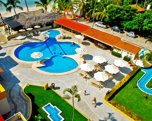 An aerial view of outdoor swimming pool with sunshade lounge near the ocean.