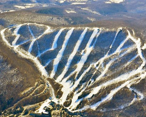 An aerial view of the Country Village slopes at Jiminy Peak covered with snow.