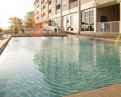 An outdoor pool alongside a multi story unit.