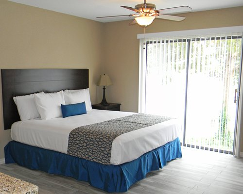 Furnished bedroom with queen bed bed and a patio.