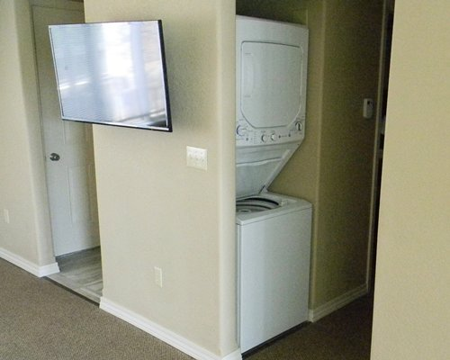 An indoor area with television and washing machine.