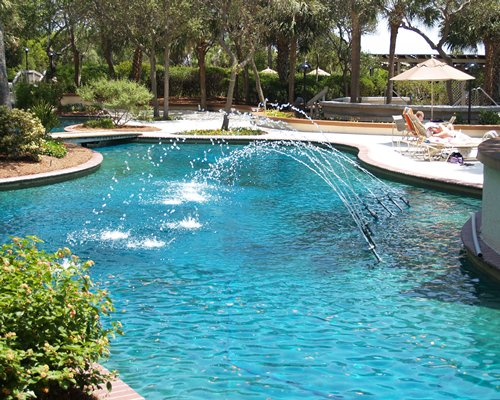 An outdoor swimming pool with multiple fountains surrounded by wooded area.