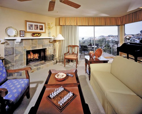 A well furnished living room with a piano fireplace and balcony with an outdoor view.