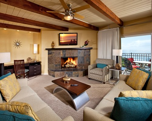 Wooded living room with double pull out sofa and a fire in the fireplace alongside the ocean.