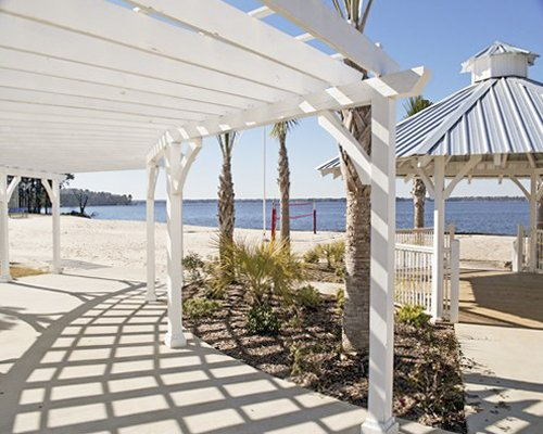 A walkway leading to the lake alongside a gazebo and beach volleyball court.