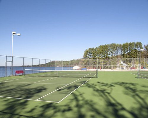 An outdoor tennis court alongside the water.