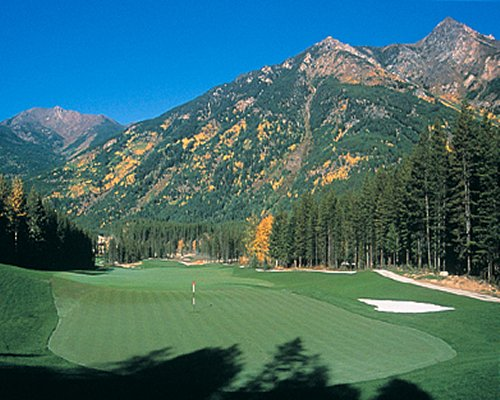 An aerial view of a well maintained golf course and mountains.