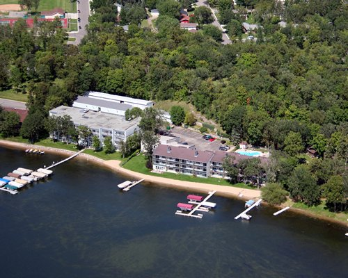 Birds eye view of Edgewater Beach Club resort alongside the lake and forested area.