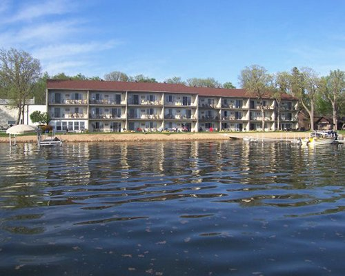 Lake view of a multi story unit surrounded by wooded area.