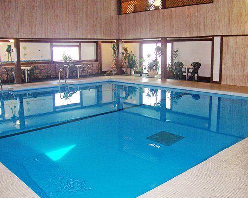 A large sized indoor swimming pool alongside patio furniture.